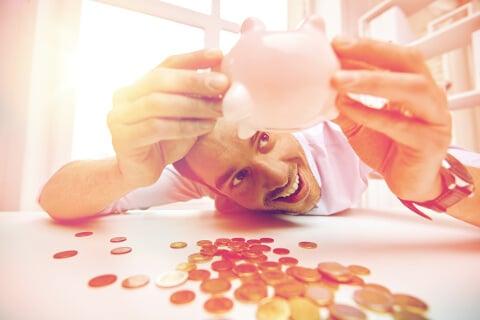 stastny muz a prasiatko s nasetrenymi peniazmi